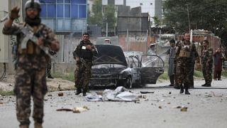Des personnels de sécurité inspectent un véhicule endommagé alors que trois roquettes ont été tirées près du palais présidentiel à Kaboul, le 20 juillet 2021