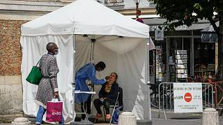 A medical technician administers nasal swabs at a mobile testing site in Versailles, west of Paris, Thursday, July 15, 2021.
