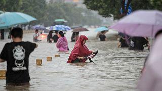 Des personnes pataugeant dans les eaux de crue le long d'une rue suite à de fortes pluies à Zhengzhou le 20 juillet 2021