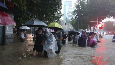 People move through flood water after a heavy downpour in Zhengzhou city, central China's Henan province on Tuesday, July 20, 2021.
