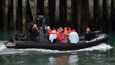 UK Border Force officials with migrants picked up in the English Channel, as they arrive in Dover, southeast England on August 15, 2020.