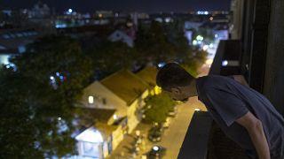 Nemanja Dragic, 36, looks at a bar across the street from his balcony in Belgrade, Serbia.