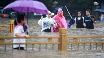People walk through floodwaters along a street in Zhengzhou in central China's Henan Province, Tuesday, July 20, 2021.