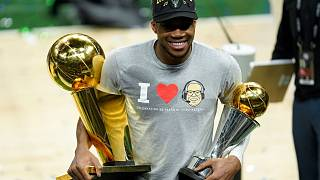 Giannis Antetokounmpo smiles while holding the NBA Championship trophy and Most Valuable Player trophy.