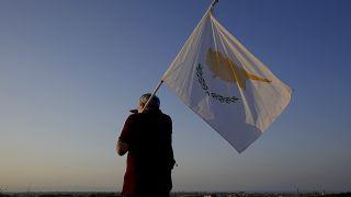 رجل يحمل علم قبرص يقف أمام فاروشا أو فاماغوستا، المدينة المهجورة   في قبرص.