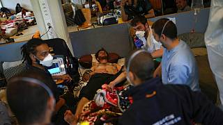 An ambulance is called for one of the migrants on hunger strike at the ULB Francophone university in Brussels on June 29, 2021