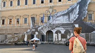 Des passants regardent l'oeuvre de JR sur la façade du palais Farnese à Rome