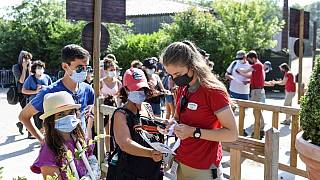An employee checks a visitors health pass at the entrance of the Puy du Fou theme park in Les Epesses, France