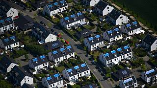 The aerial view shows a housing estate with solar panels on the roof in Duesseldorf, western Germany