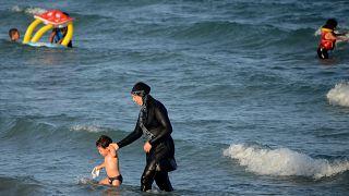 "A Tunisian woman wearing a ""burkini"", a full-body swimsuit designed for Muslim women"