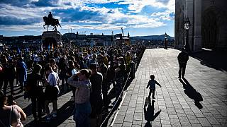 A man walks with a child in front of the parliament building in Budapest during a demonstration