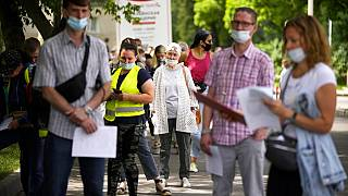 People wait in line to receive the COVID-19 jab at a Moscow vaccination centre in July
