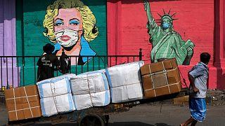 کارگر هندی محو تماشای نقاشی دیواری از مجسمه آزادی و مرلین مونروی ماسک زده