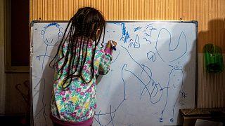 Koronavirüs nedeniyle iki ay önce kaybettiği 37 yaşındaki annesi Silvia Cano'nun resmini çizen küçük kız Kehity Collantes. Santiago/ Şili