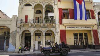 دورية للشرطة الكوبية أمام علم كوبي كبير يتدلى من واجهة مبنى في هافانا، كوبا.