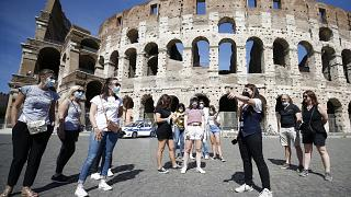 Tourists wear face masks to curb the spread of COVID-19 as they listen to a tour guide outside the ancient Colosseum, in Rome, May 21, 2021.