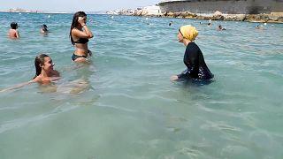Imágen de archivo de 2016: Nesrine Kenza, que dice estar feliz de ser libre de llevar un burkini, y dos amigos no identificados se adentran en el mar, en Marsella, Francia.