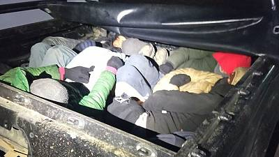 Migrants in the back of a vehicle stopped during the police operation