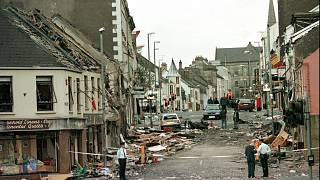 Royal Ulster Constabulary Police officers stand on Market Street at the scene of a car bombing.
