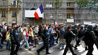 French riot mobile gendarmes walk past protesters