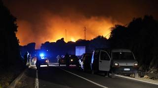 Cars are parked by the road as fires have been raging through the countryside in Cuglieri, near Oristano, Sardinia, Italy, July 25, 2021.