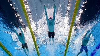 Britain's Adam Peaty, center, swims to win the gold medal in the 100-meter breaststroke final at the 2020 Summer Olympics, July 26, 2021, in Tokyo.