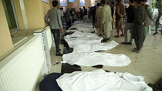 رجال أفغان يحاولون التعرف على الجثث في مستشفى بعد انفجار قاتل بالقرب من مدرسة غرب كابول، أفغانستان.