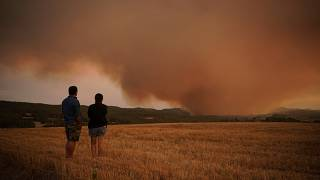 Residents look on as athe forest fire rages near Tarragona.