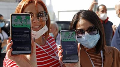 """Attendees show off their """"green passes"""" (proof of being fully vaccinated against COVID-19 coronavirus disease) as they arrive at Bloomfield Stadium in Israel."""