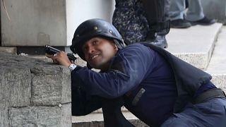 Un miembro de las fuerzas de seguridad venezolanas se protege de los disparos
