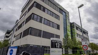 """FILE - In this May 6, 2021 file photo a man with a face mask leaves the headquarters of the German biotechnology company """"BioNTech"""" in Mainz, Germany."""