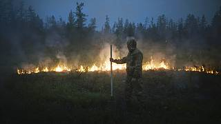 A member of volunteers crew walks past a burning grass near the edge of the fire at Gorny Ulus area west of Yakutsk, Russia, Thursday, July 22, 2021.