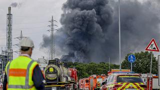 Emergency vehicles stand not far from an access road to the Chempark over which a dark cloud of smoke is rising in Leverkusen, Germany, July 27, 2021.