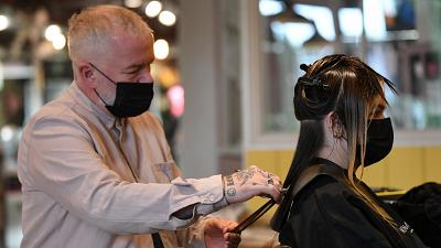 Salon owner and hairdresser Adam Reed cuts a client's hair at his salon in Spitalfields, East London on July 1, 2021.