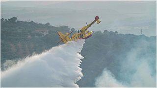 """طائرة من طراز""""كانداير"""" تلقي مواد لإخماد النيران بالقرب من منطقة أوريستانو في جزيرة سردينيا الإيطالية، الاثنين 26  تموز/يوليو 2021"""