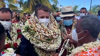 Emmanuel Macron is welcomed with garlands of flowers and seashells on Manihi Island