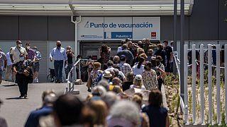 Emberek állnak sorba egy madridi kórház oltási pontjánál