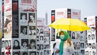 FILE: A woman walks past some of the thousands photos of people killed in Iran during the 1988 massacre of political prisoners, Washington DC, Sept. 2020.