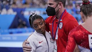 Coach Laurent Landi embraces Simone Biles, after she exited the team final, at the 2020 Summer Olympics, Tuesday, July 27, 2021, in Tokyo