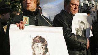 un manifestante tiene un ritratto di Anna Politkovskaya durante una manifestazione non autorizzata del 2006 per commemorare i giornalisti uccisi in Russia