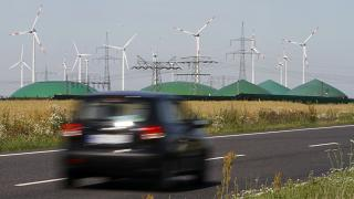 A car passes by a biogas plant and windmills near Nauen, Germany.