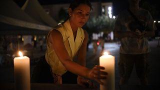 Eine Frau stellt in Pristina in Gedenken an die Opfer eine Kerze auf