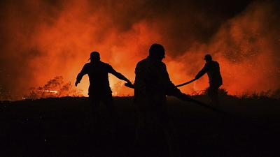 Firefighters and local villagers try to bring a fire under control in the village of Kirli.