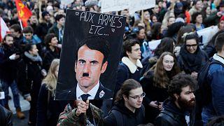 متظاهر ضد ماكرون يحمل لافتة تشبه الرئيس بهتلر