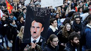 A person holds a placard depicting French President Emmanuel Macron as Adolf Hitler during a 2018 protest against a proposed university reform.