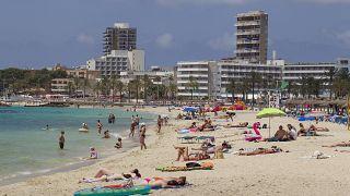 Sonnenanbeter am Strand von Magaluf auf der balearischen Insel Mallorca