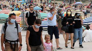 Persone che indossano maschere per proteggersi dal coronavirus camminano sulla passeggiata pedonale lungo la spiaggia di Biarritz, nel sud-ovest della Francia, 28 luglio 2021