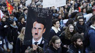 un cartello raffigurante il presidente francese Emmanuel Macron nei panni di Adolf Hitler durante una protesta del 2018 contro una proposta di riforma universitaria
