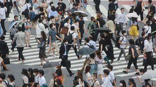 People wearing face masks cross a street in Tokyo