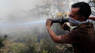 Önkéntes tűzoltó küzd a lángokkal a libanoni Akkar tartományban 2021. július 29-én